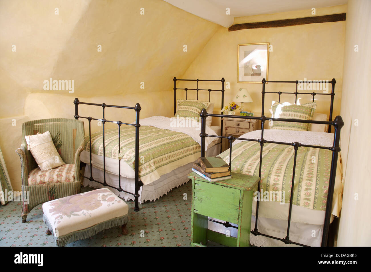 Wrought iron twin beds with green throws in attic bedroom with ...