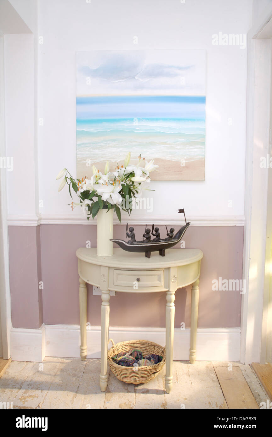 Seascape painting on wall above painted half moon table with vase seascape painting on wall above painted half moon table with vase of white lilies in country hall with mauve dado reviewsmspy