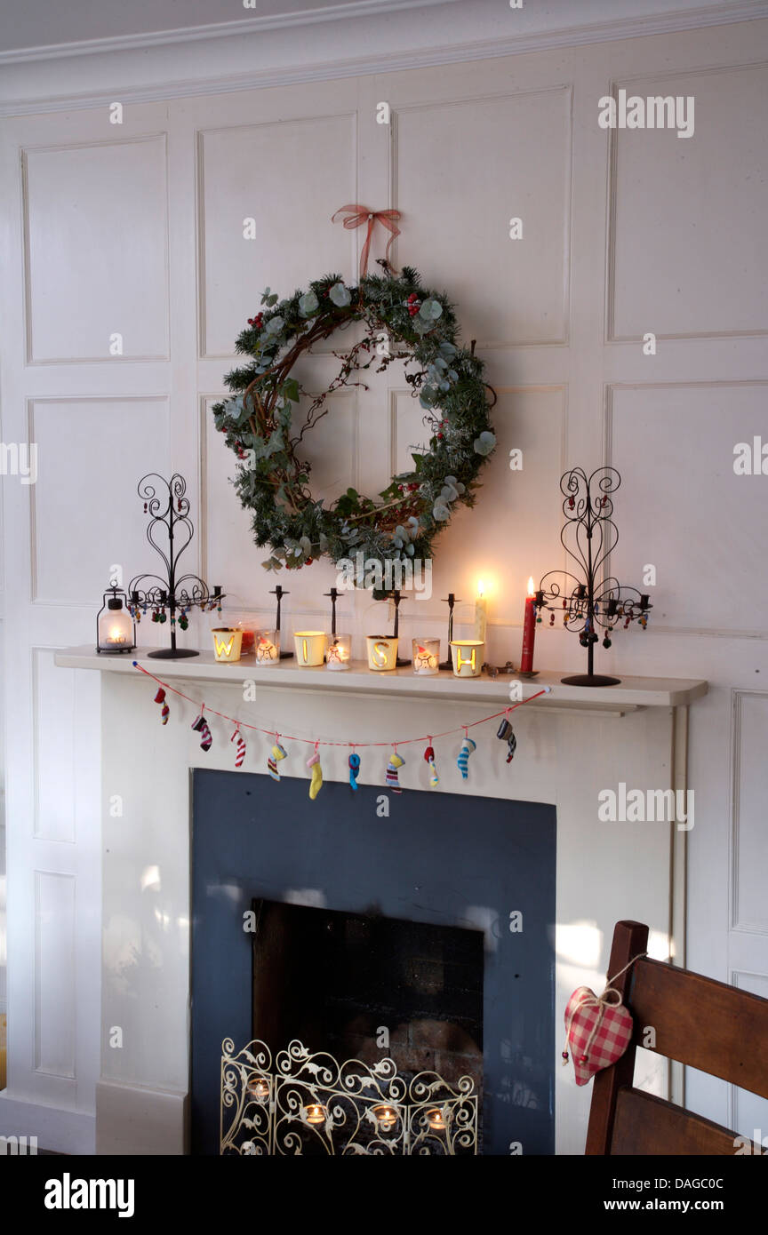 ivy and conifer wreath above fireplace in white paneled dining