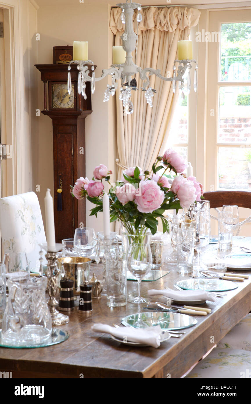 Glass Chandelier Above Table Set For Lunch With Vase Of Pink Peonies In Country Dining Room Cream Drapes On French Windows
