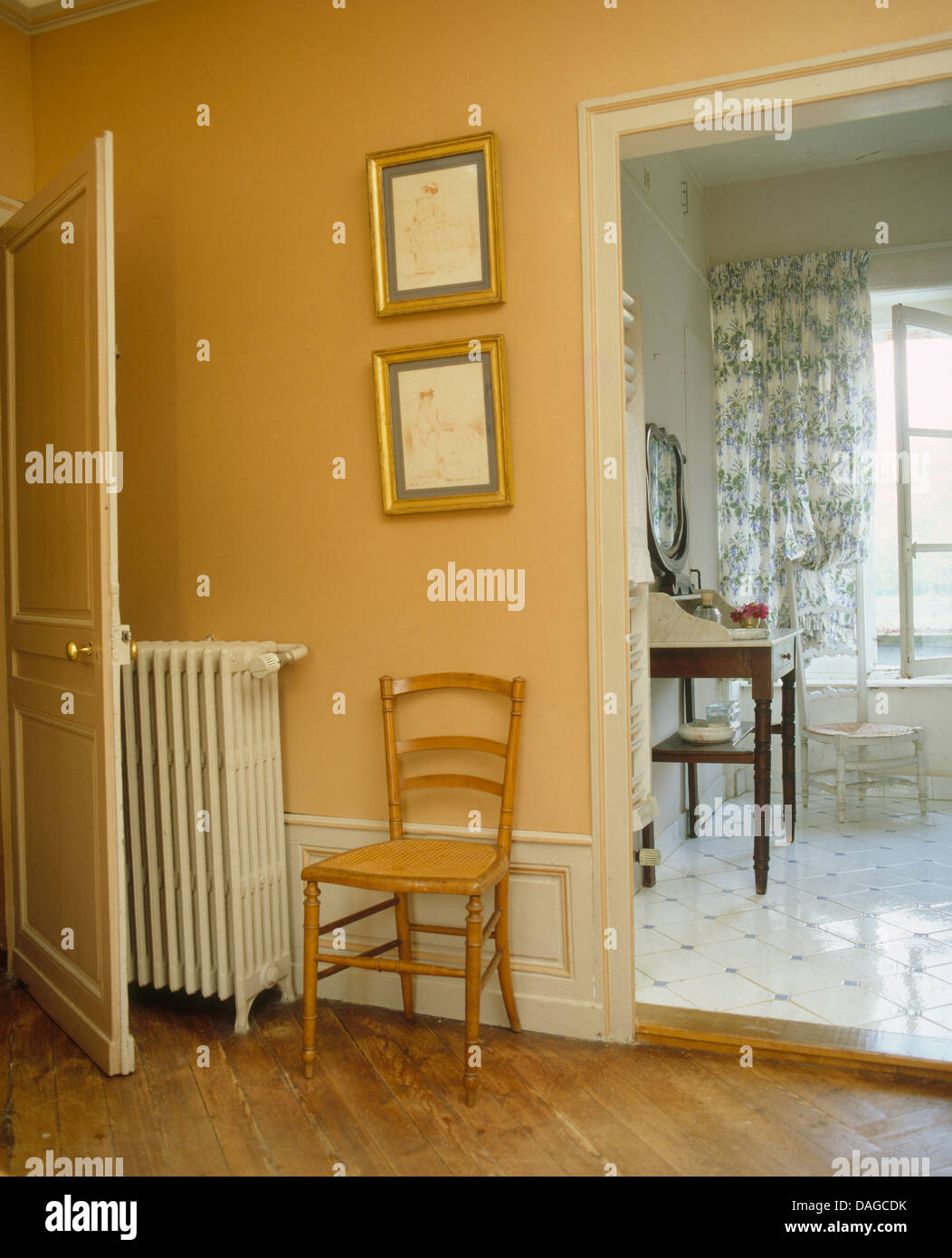 French country bedroom with simple wooden chair beside radiator