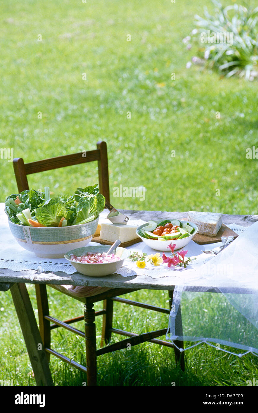 Wooden chair at simple table set for lunch on the lawn Simple table setting for lunch