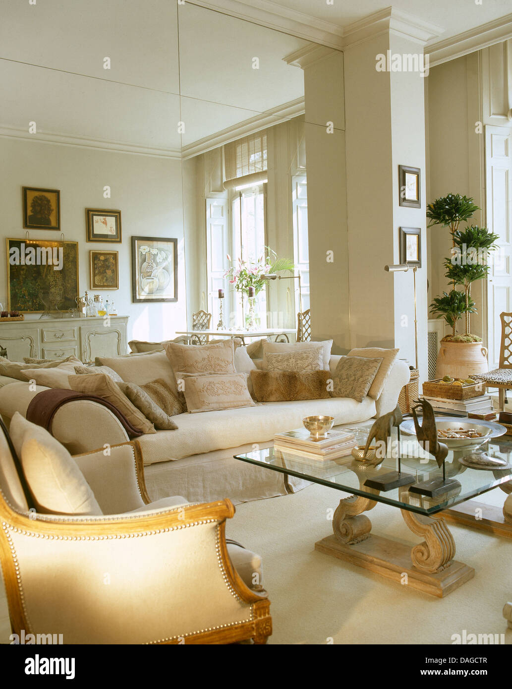 mirrored wall behind cream sofa in town house living room with glass