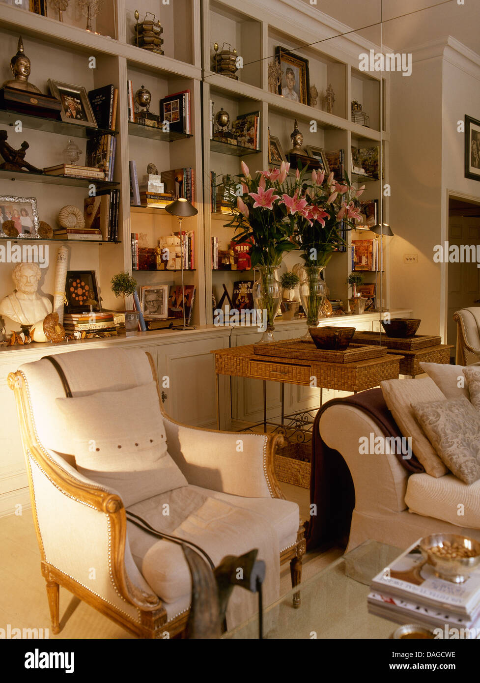Cream Armchair And Sofa In Front Of Fitted Shelves With Lighted Spotlights Apartment Living Room