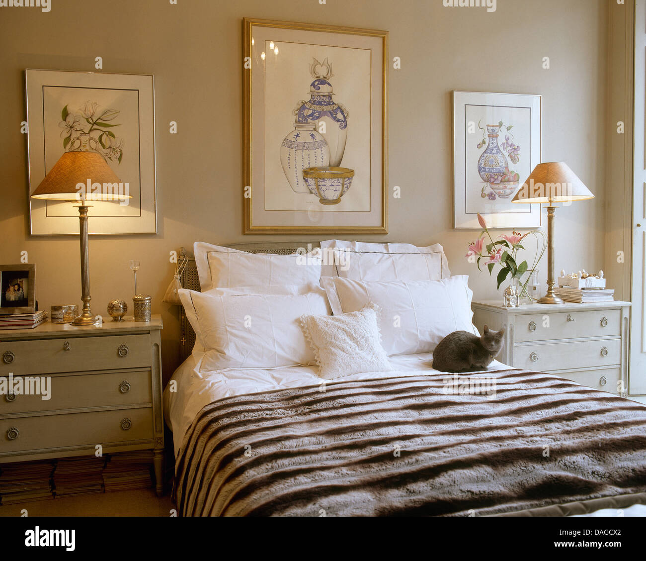 cat bedroom. Cat sitting on bed with white pillows and faux fur throw in bedroom  lit bedside lamps cabinets either side of
