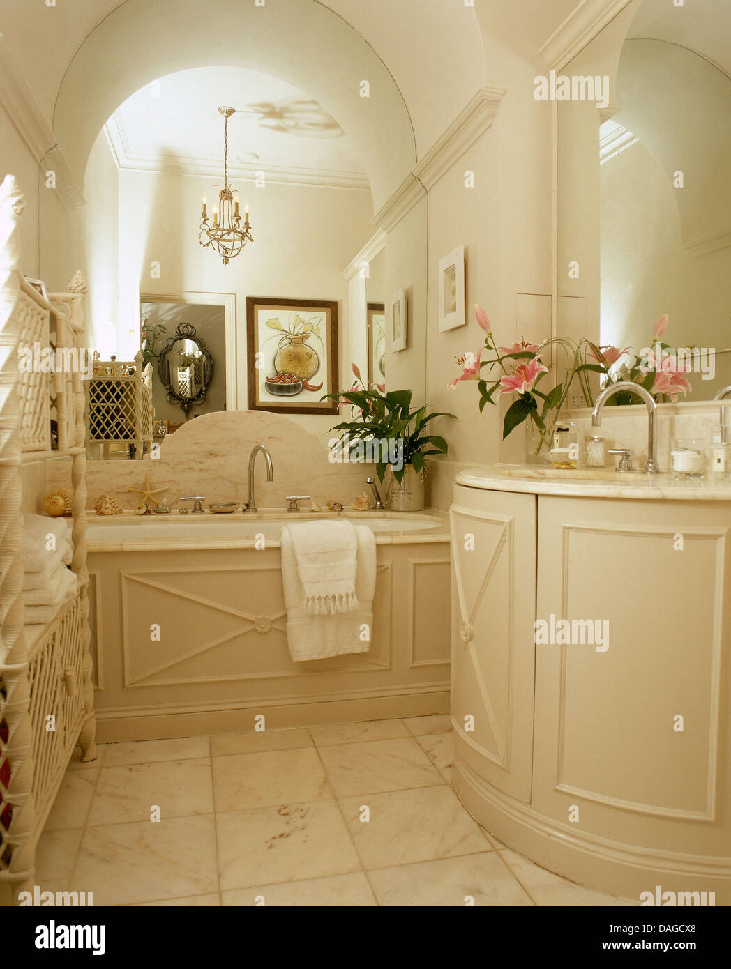 Basin In Curved Vanity Unit In Cream Town House Bathroom With Mirrored Wall  Above Panelled Bath
