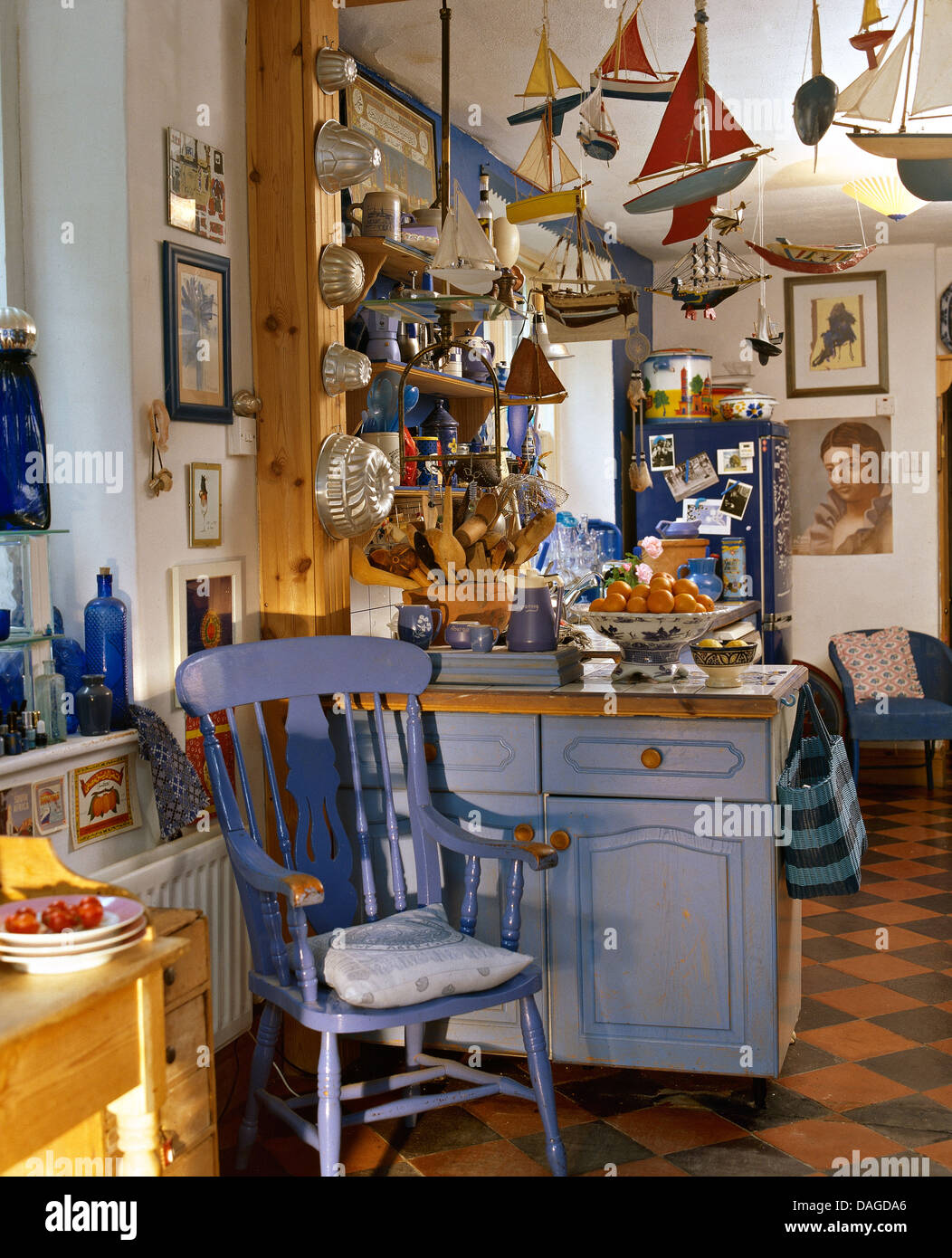 Blue Painted Windsor Chair Beside Blue Fitted Unit In Cluttered Cottage  Kitchen With Toy Sailing Boats Hanging From Ceiling