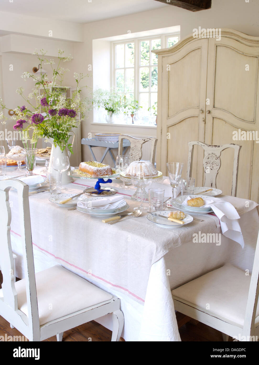 White Linen Cloth On Table Set For Lunch In Country Dining Room With Painted Chairs And Cupboard