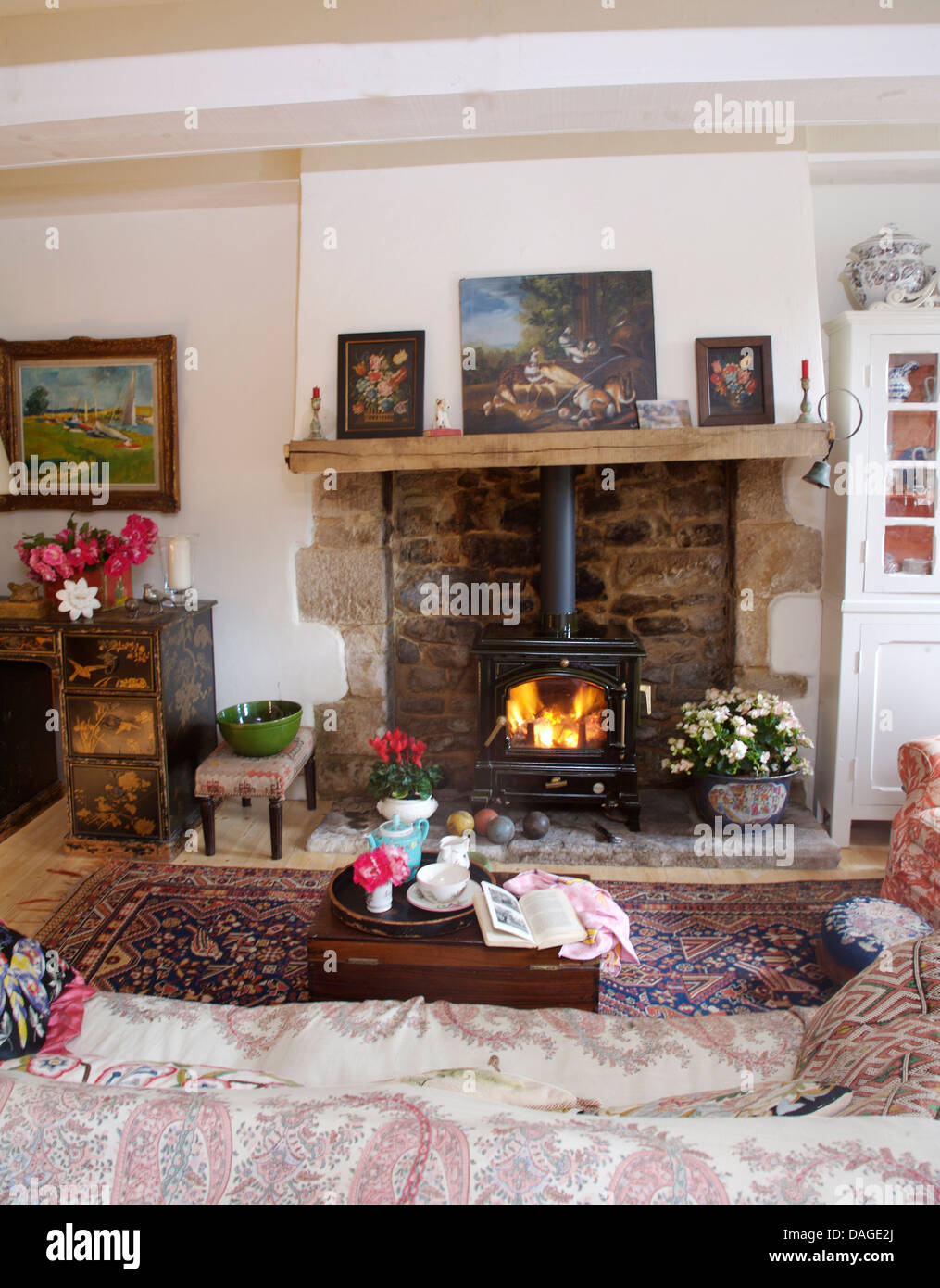 pictures on wooden mantelpiece above fireplace with lit wood
