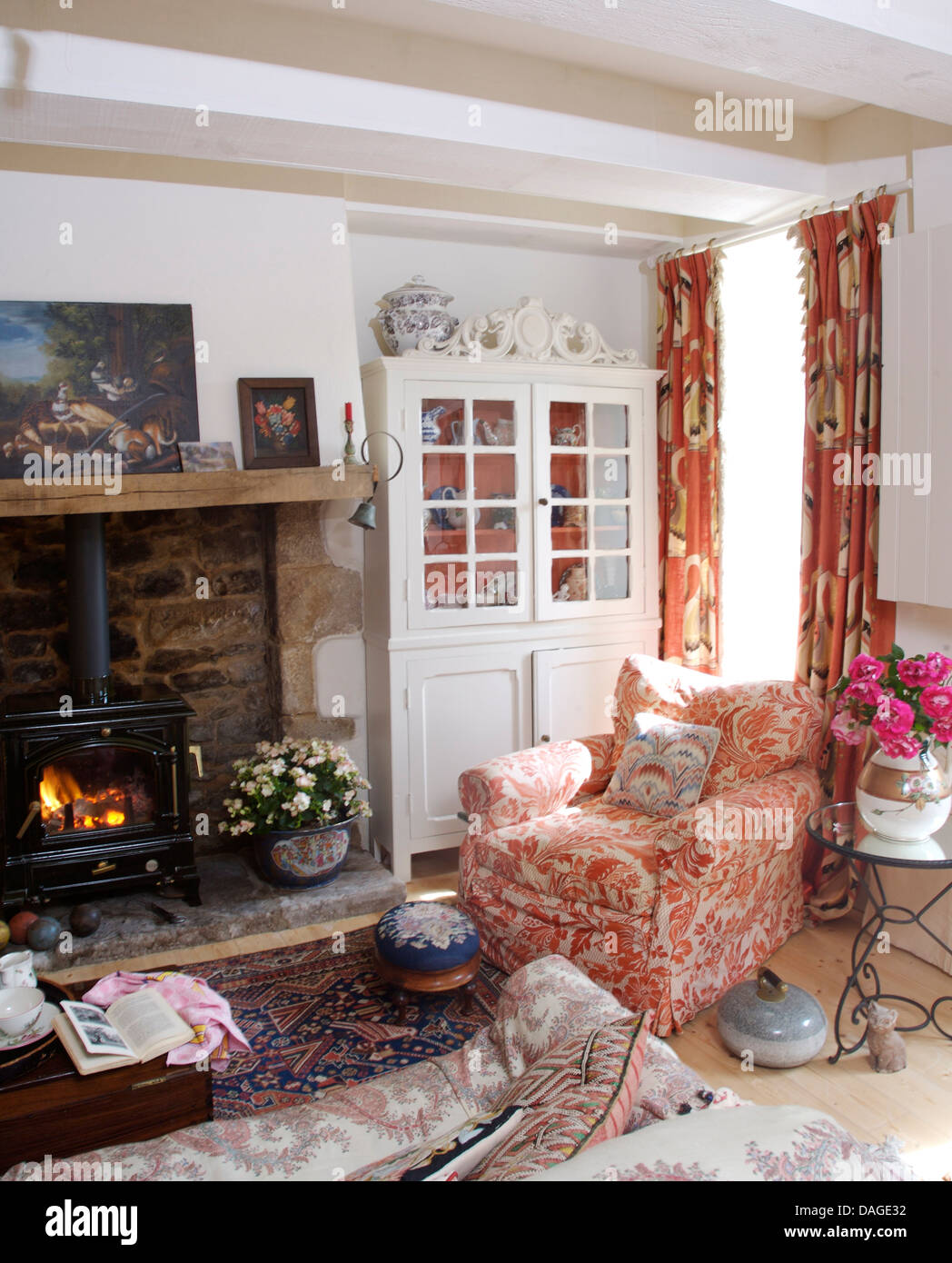 pink white armchair beside fireplace with wood burning stove in