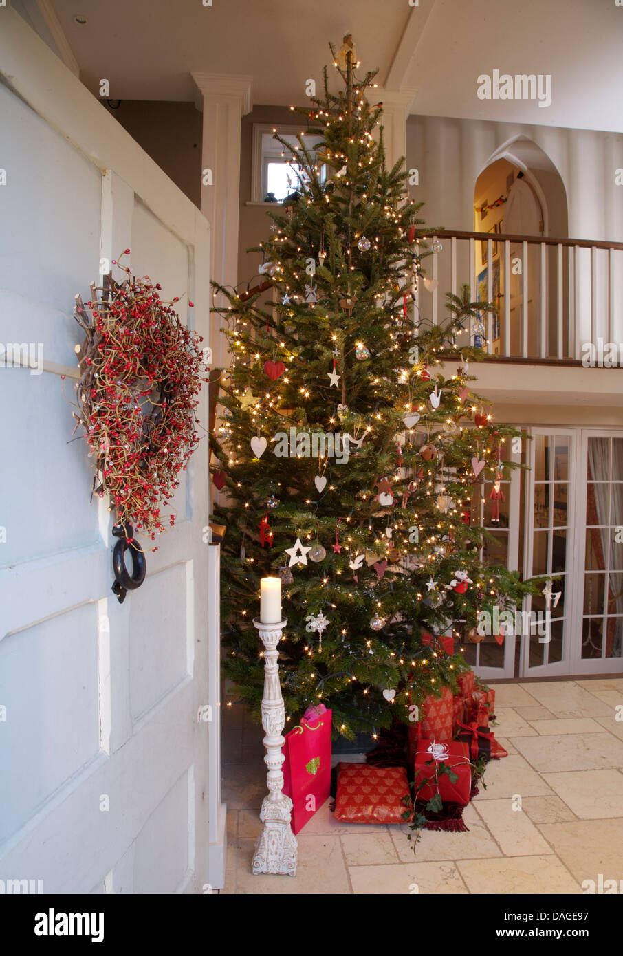stock photo wreath on open front door with view of tall christmas tree and gift wrapped presents in double height country hall - Tall Christmas Tree