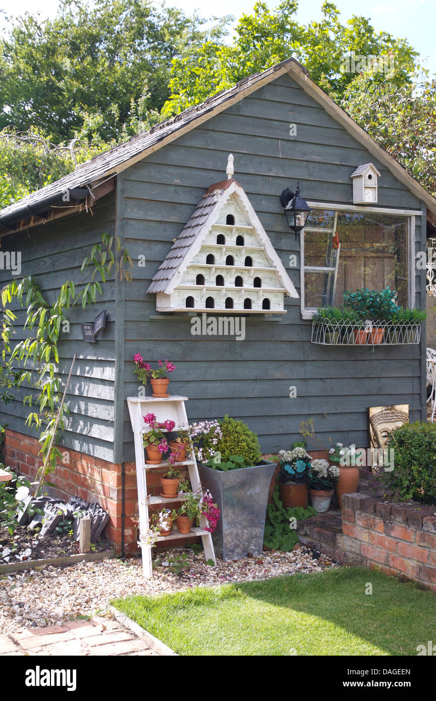 gray painted garden shed with white dove cote above pots on white painted step ladder in country garden