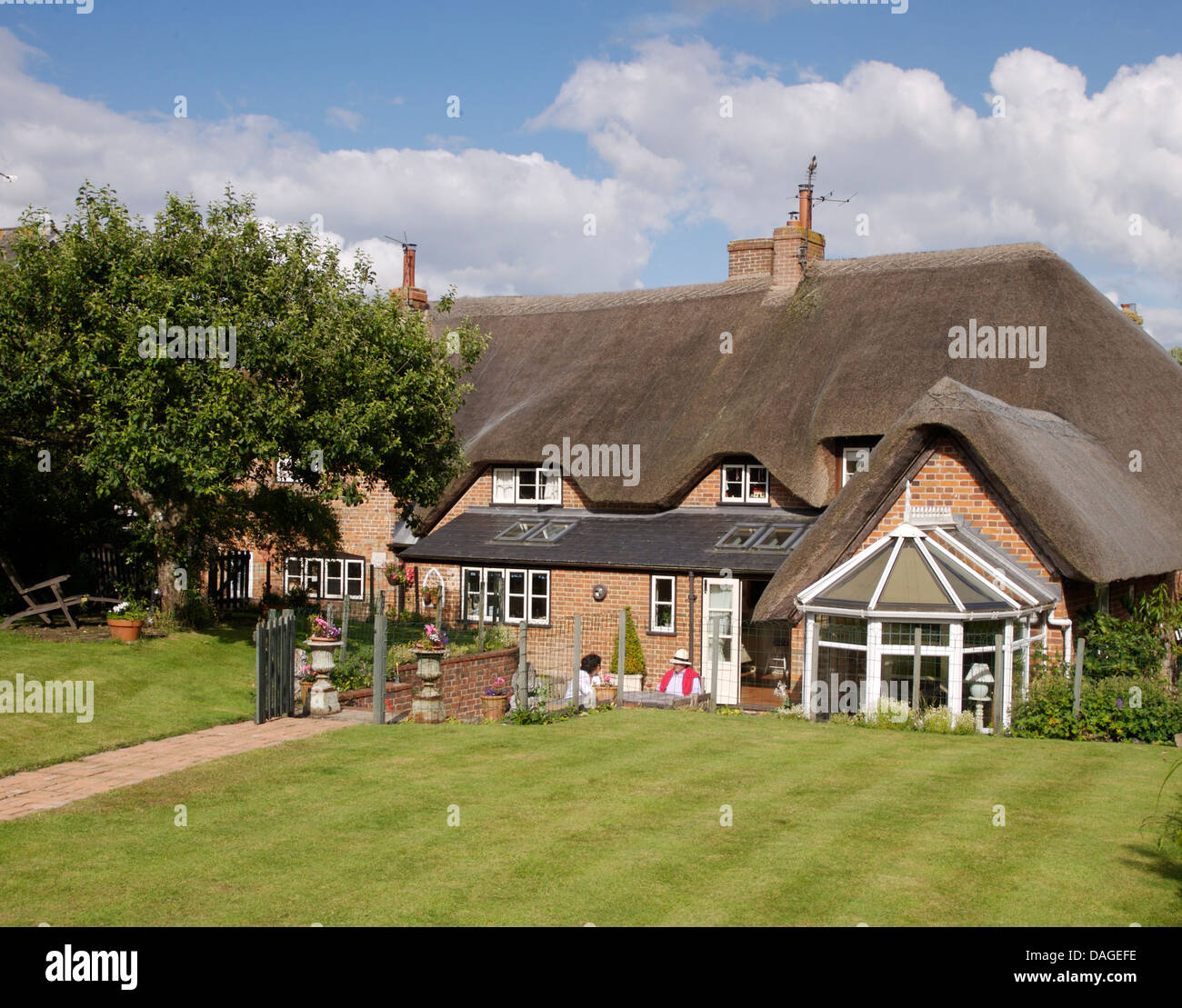 Lawn In Front Of Large Country Cottage With Thatched Roof