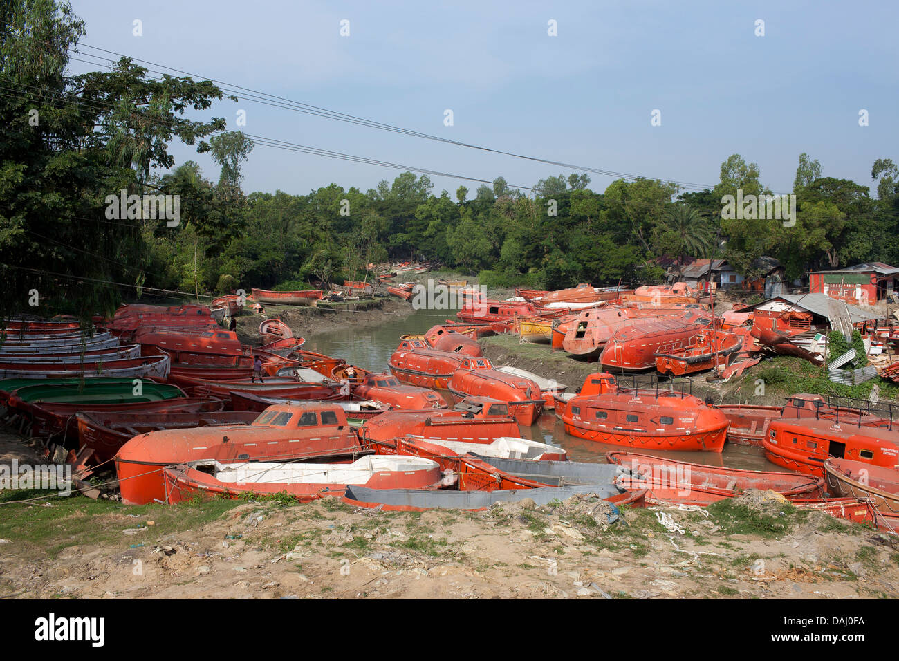 Old discarded bright orange life boats from ships for sale close ...