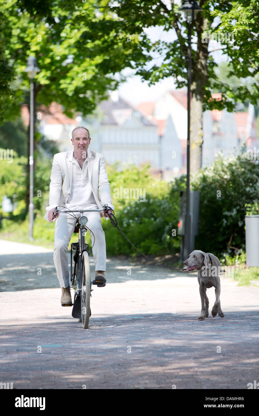 germany, bavaria, portrait of mature man riding bicycle with stock