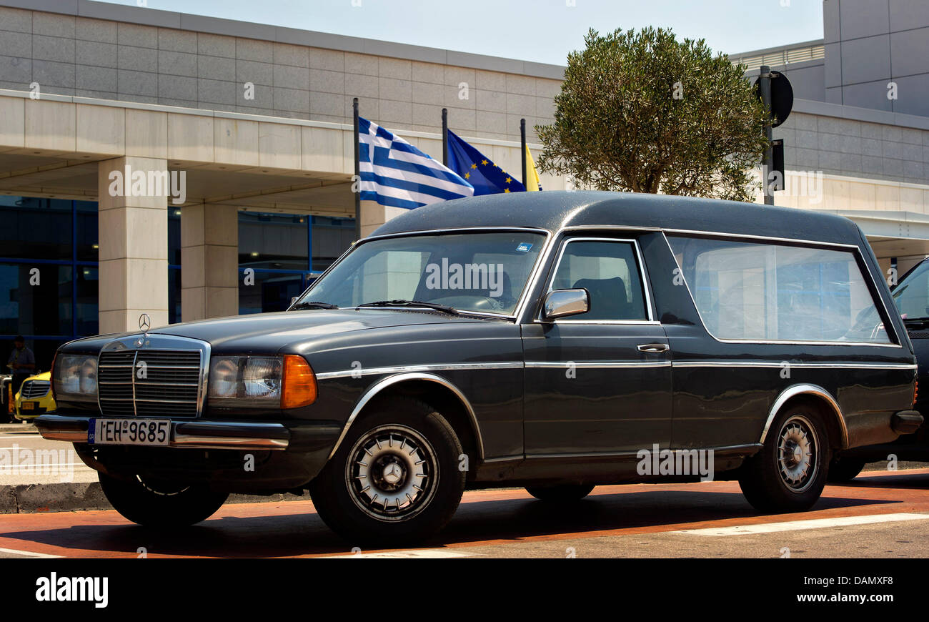 An old mercedes benz hearse stands in front of a greek for Mercedes benz hearse