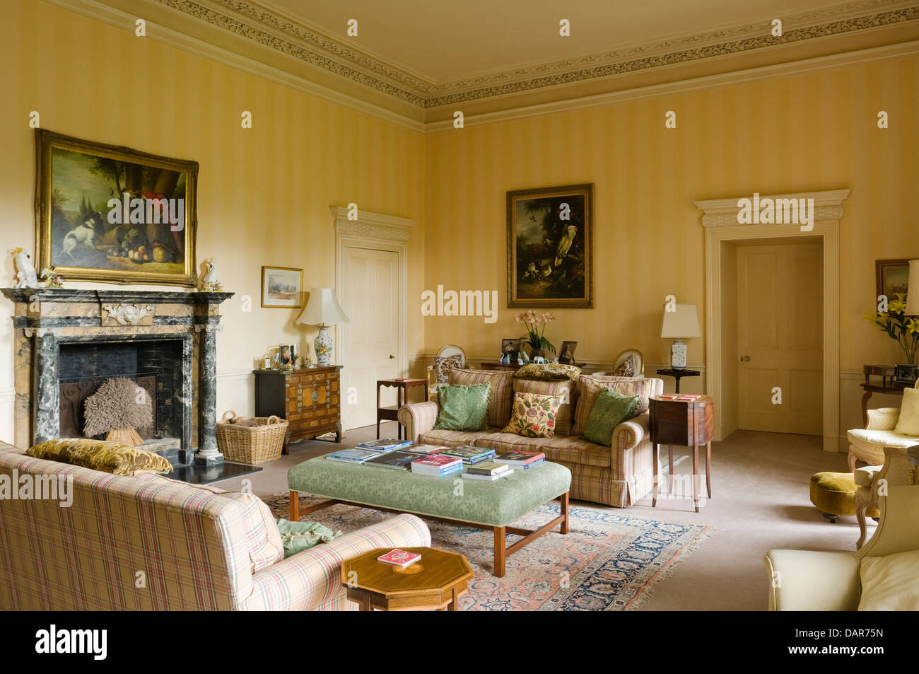 yellow reception room with marble fireplace and green ottoman