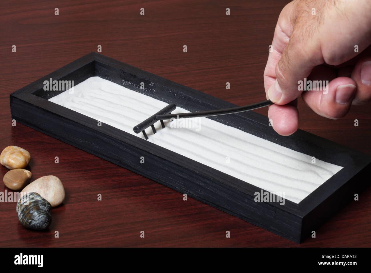 Man Raking Sand In A Miniature Table Top Zen Garden