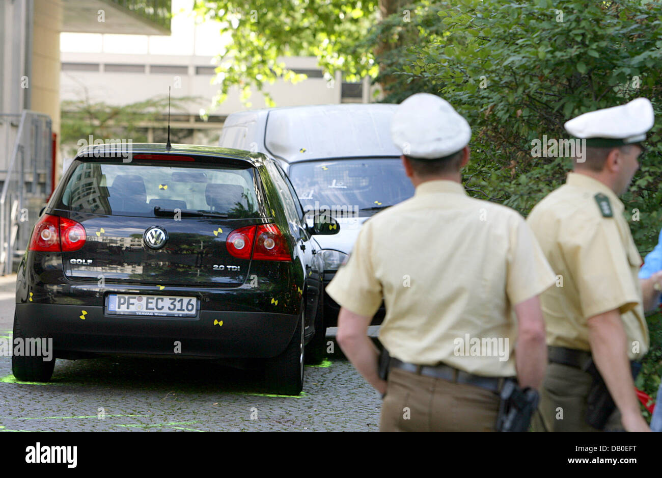 Policemen guard two cordoned-off cars, in which the bodies of five ...