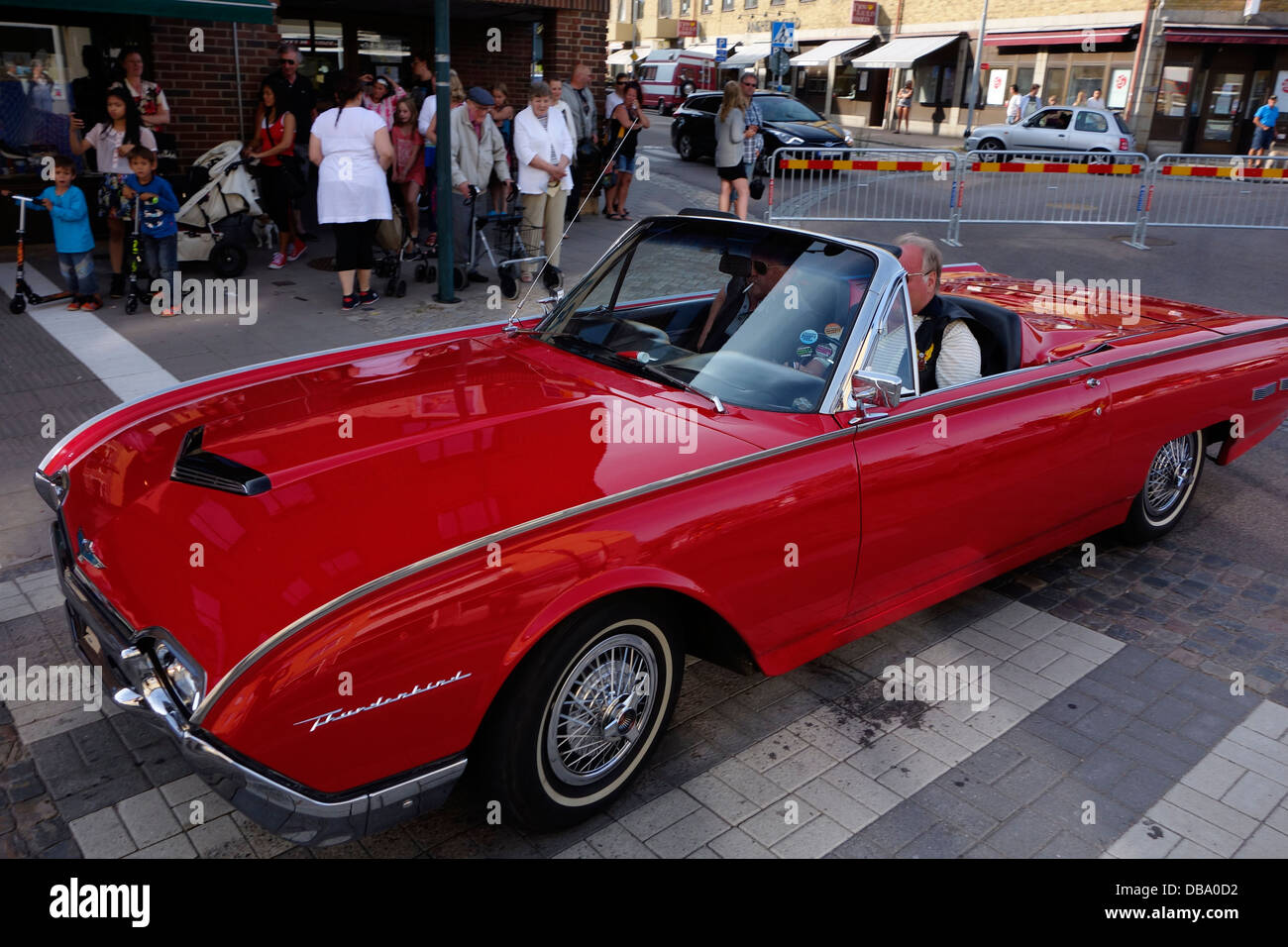 Two Elderly Men Ride In The Red (1962) Ford Thunderbird Sports Roadster  Classic Car. On The Road In Varberg Town, Sweden
