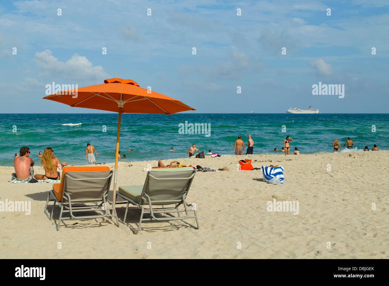 Nice Beach Chairs, Orange Sun Umbrella And Many Happy Beach Goers At South Beach,  Miami Florida. A Cruise Ship Is In The Distance.