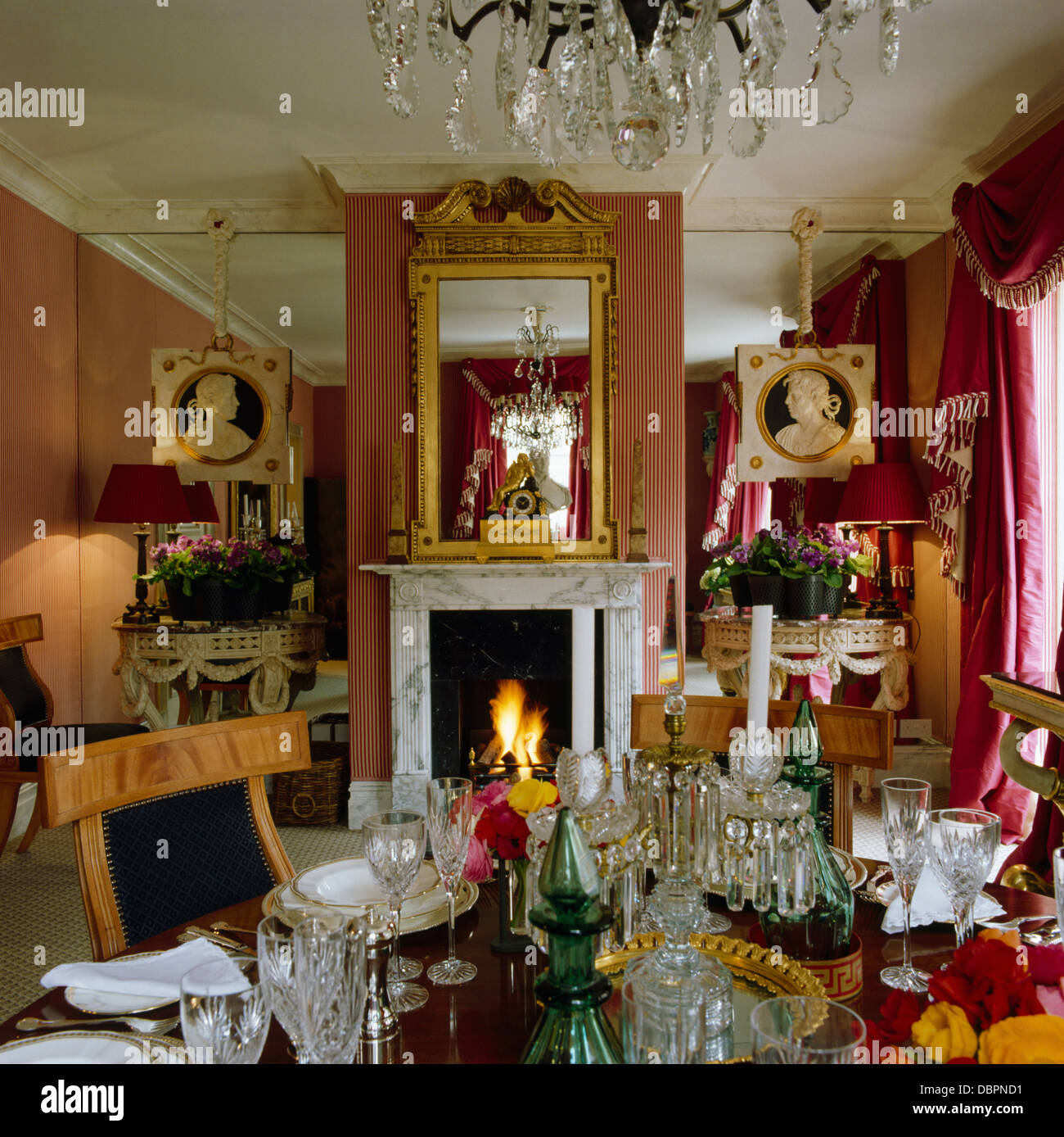 Mirrored Alcoves On Either Side Of Fireplace Below Antique Mirror In Elegant Red Dining Room With Table Set For Lunch