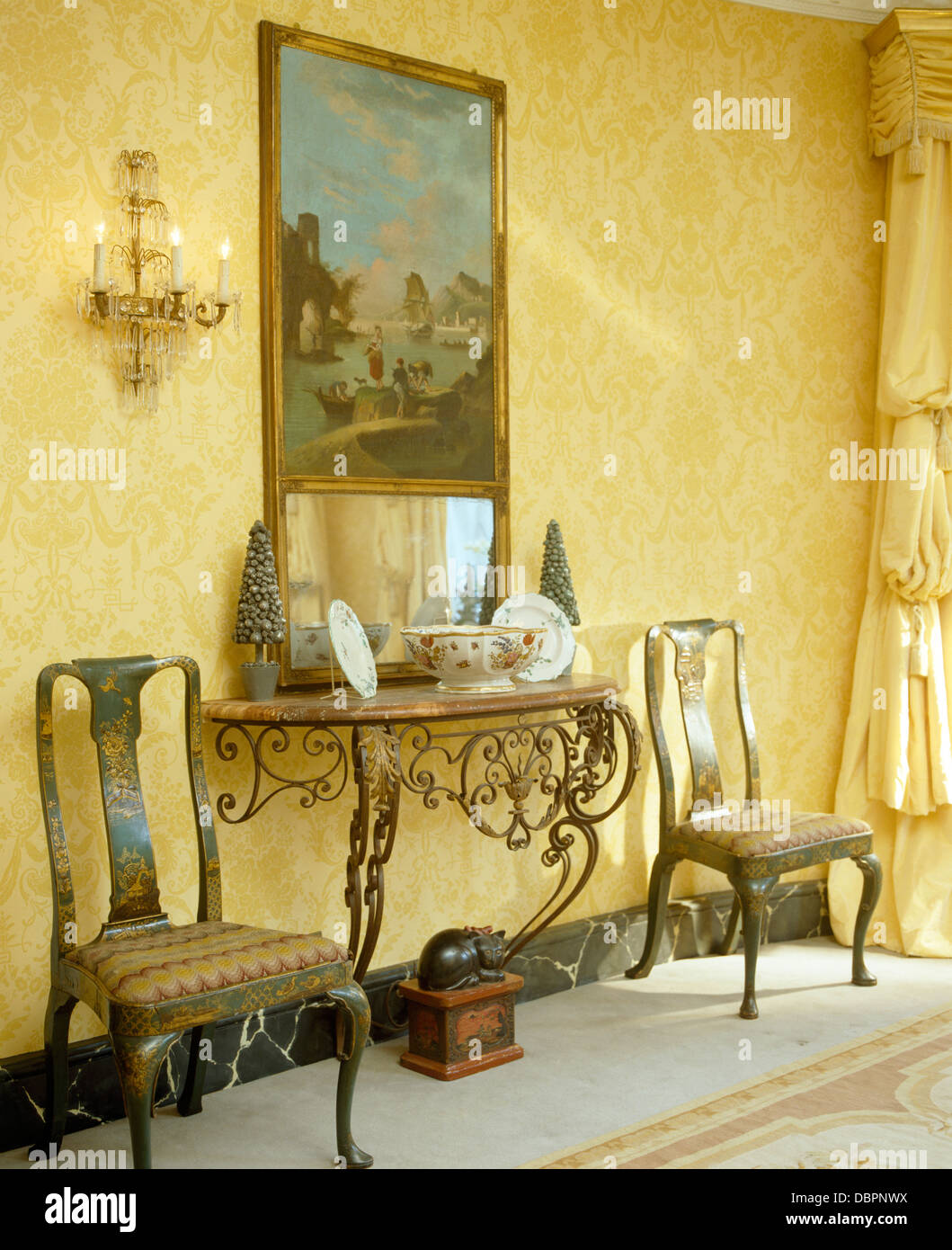 Large painting above marblemetal console table in hall with large painting above marblemetal console table in hall with painted antique chairs and damask wallpaper geotapseo Choice Image
