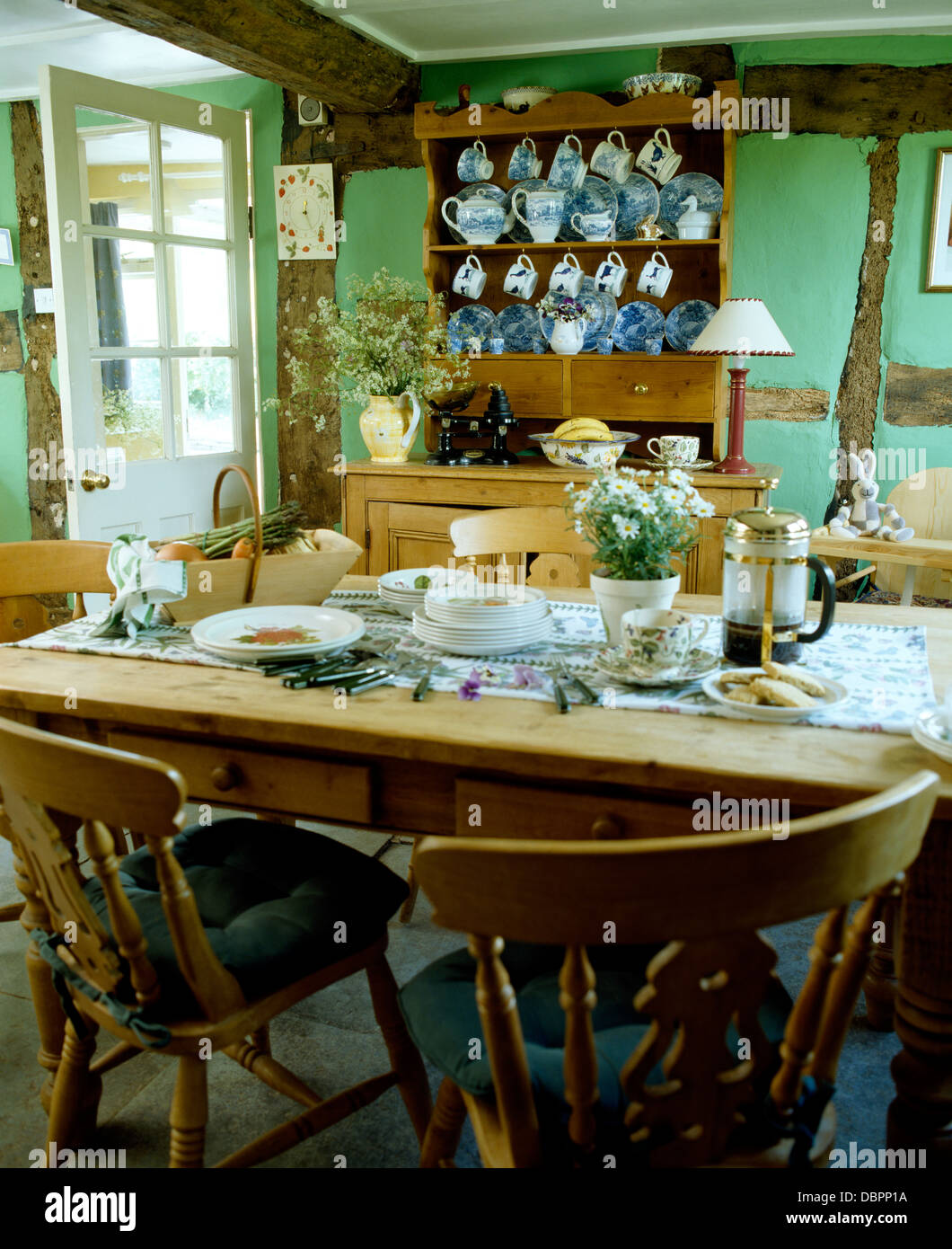 Pine Chairs At Pine Table Set For Breakfast In Pale Green Country Dining  Room With Blue+white China On Pine Dresser