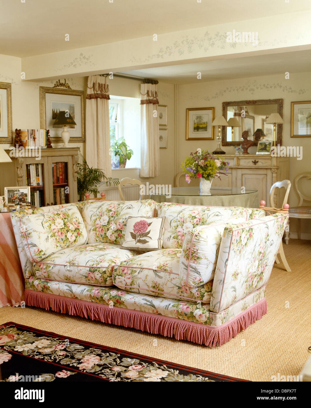 Floral sofa with pink fringed edging in cottage living and dining