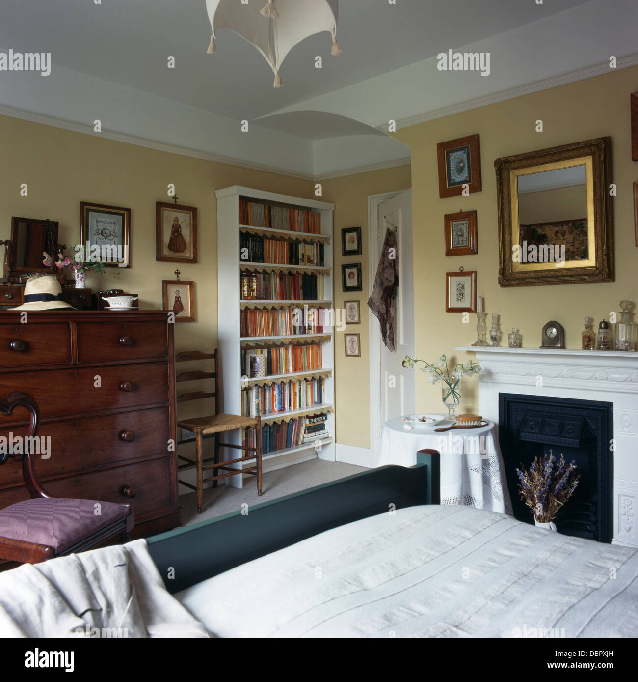Freestanding White Bookshelves And Antique Chest Of Drawers In Townhouse  Bedroom With Mirror Above Fireplace