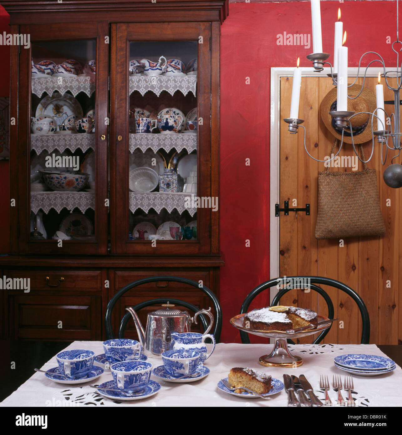Table Set For Tea With Blue White China In Red Cottage Dining Room Glass Front Dresser And Candle Chandelier