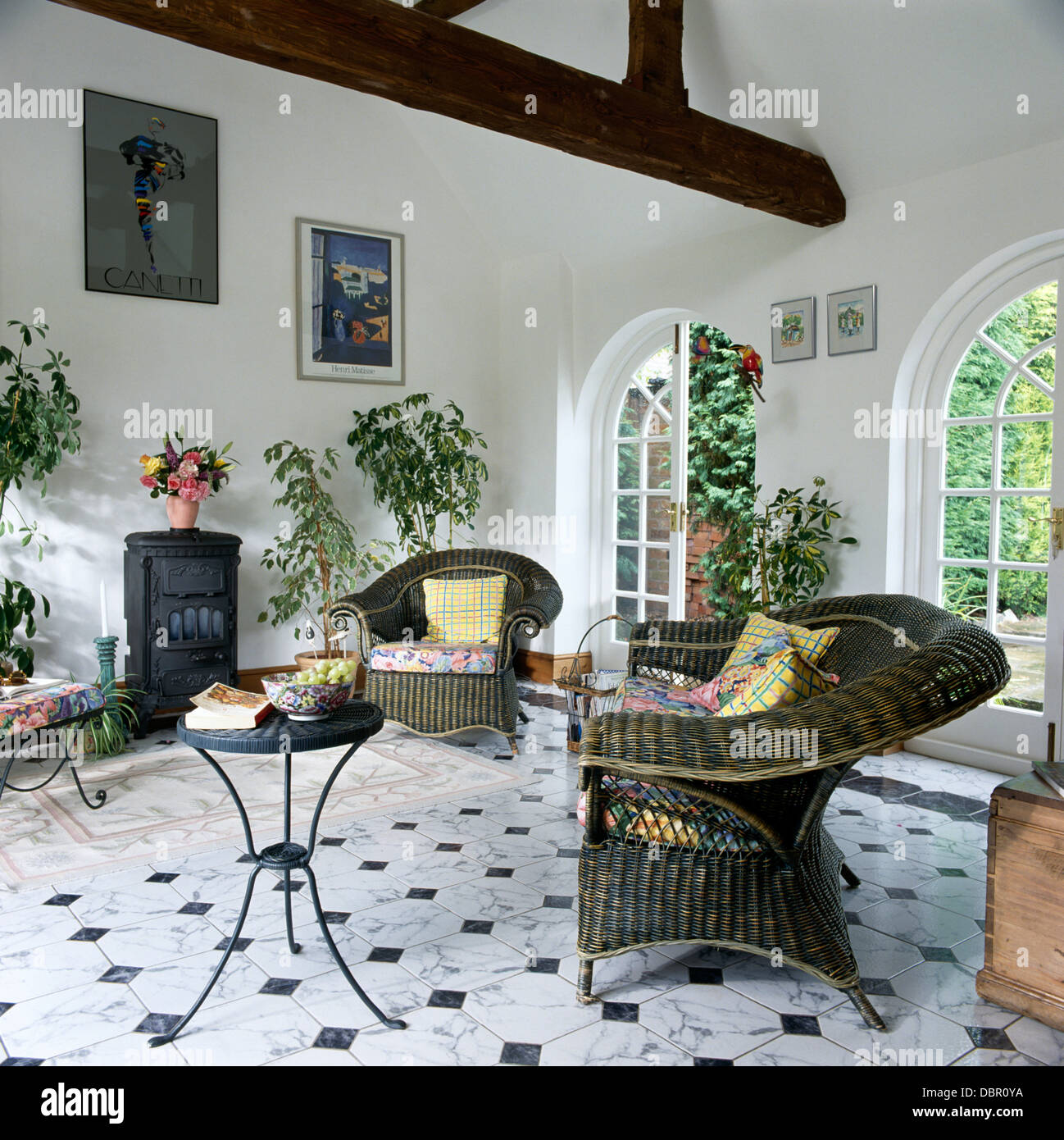 grey wicker armchairs and small metal table in white
