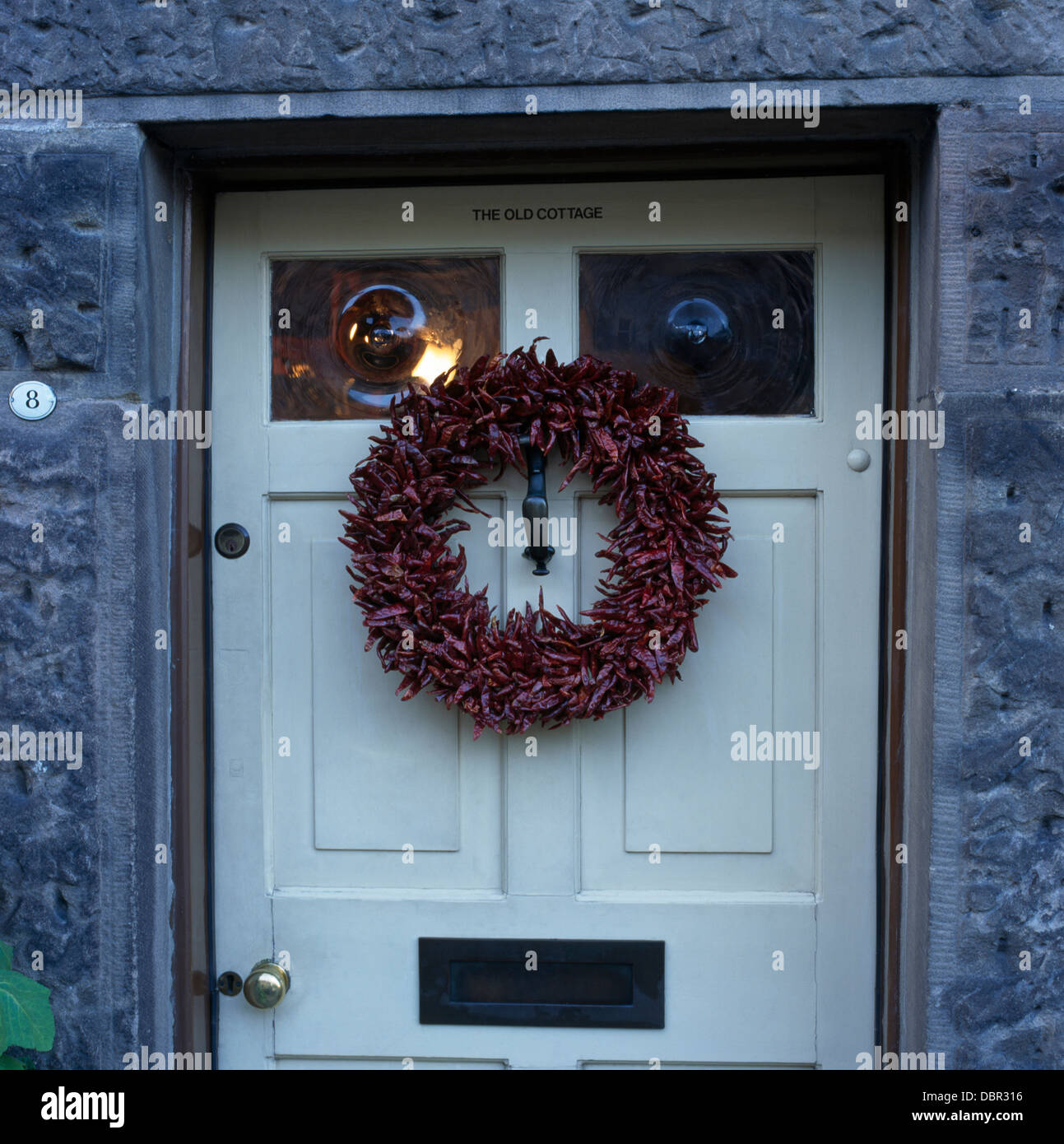 Close-up of dried red chilli Christmas wreath on white front door ...