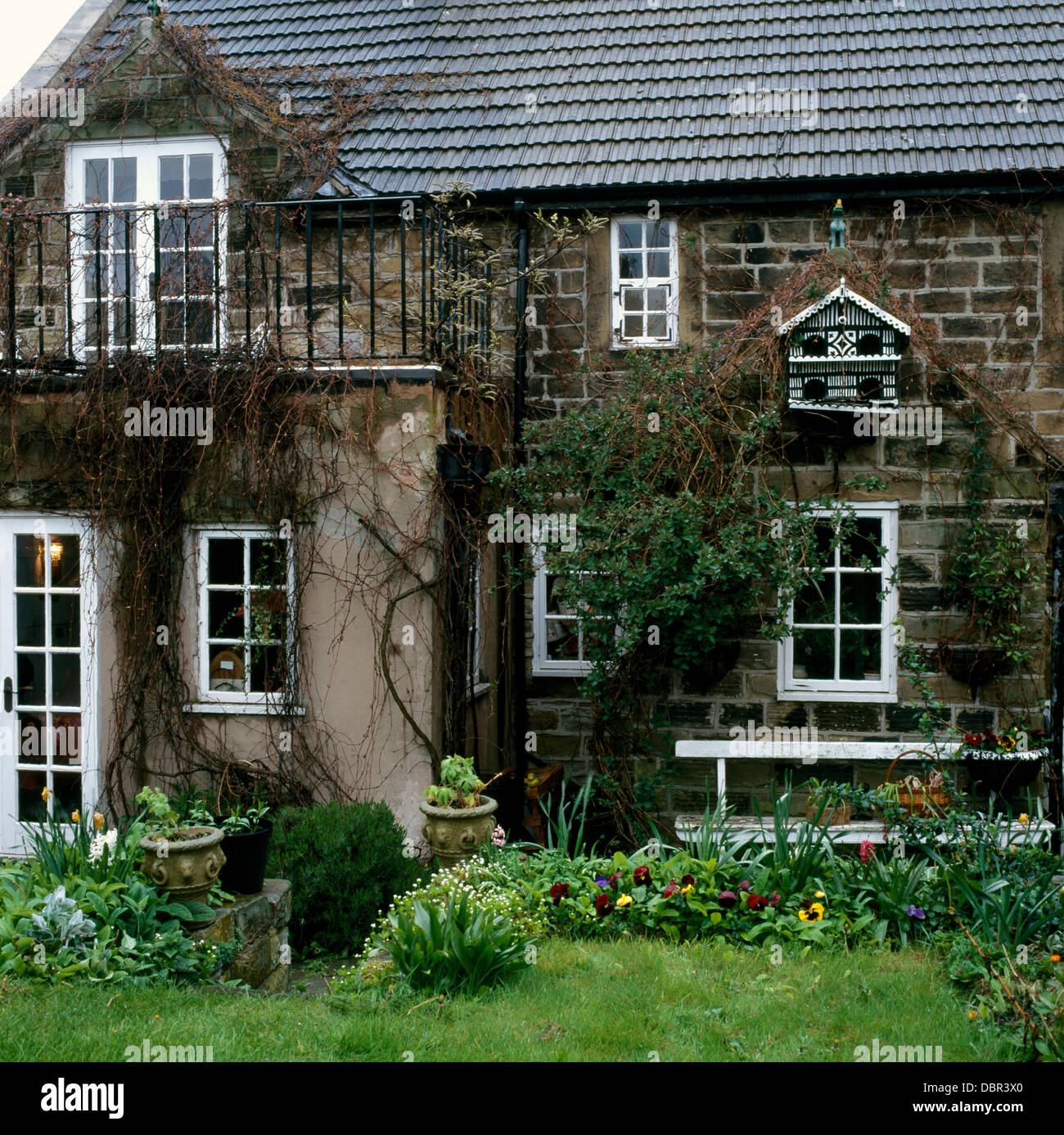 old dovecote on wall of small stone country house with balcony old dovecote on wall of small stone country house with balcony above french windows