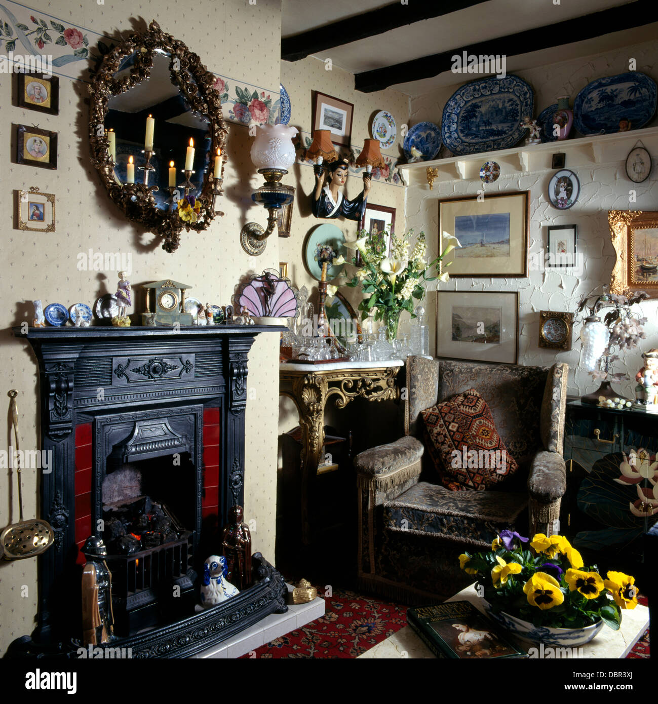 Girandole Mirror With Lighted Candles Above Cast Iron Fireplace In Small Cluttered Victorian Living