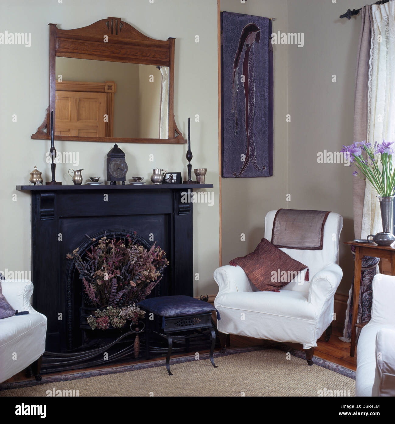 Edwardian Wood Framed Mirror Above Black Fireplace In Small White Living Room With Loose Cover On Armchair