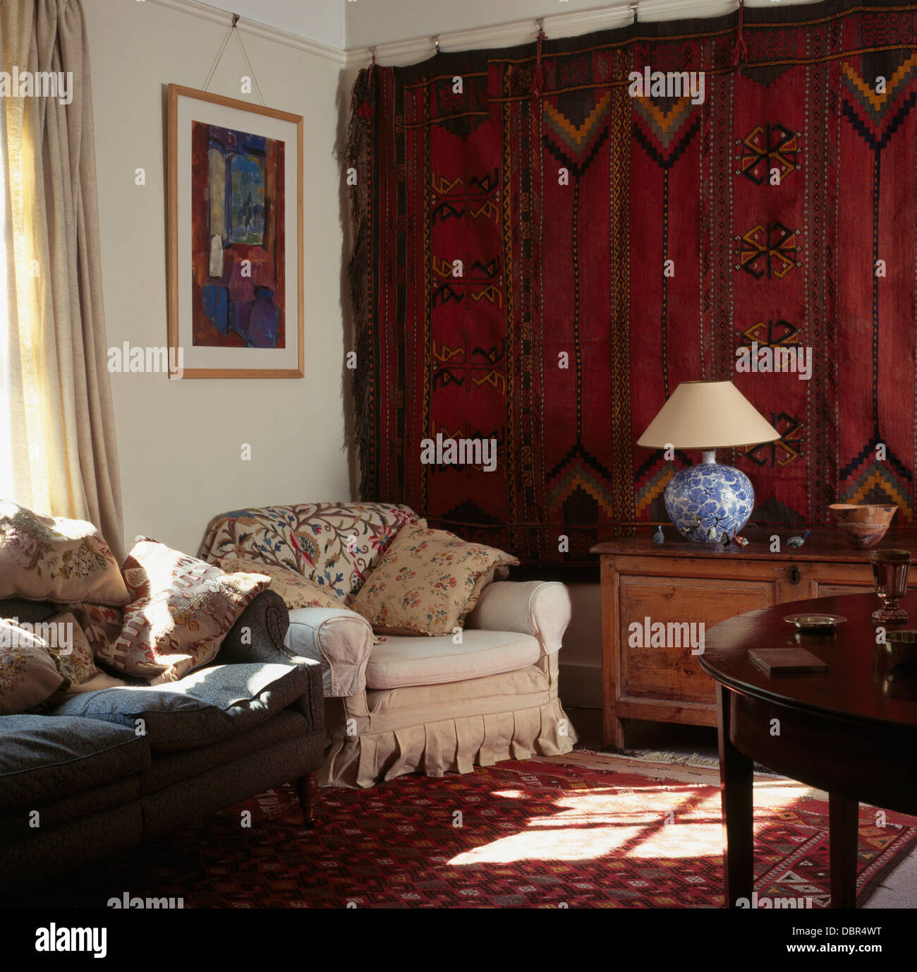 Old Red Persian Carpet Hanging On Wall In Townhouse Living Room With Cream Armchair And Gray Sofa Piled Cushions