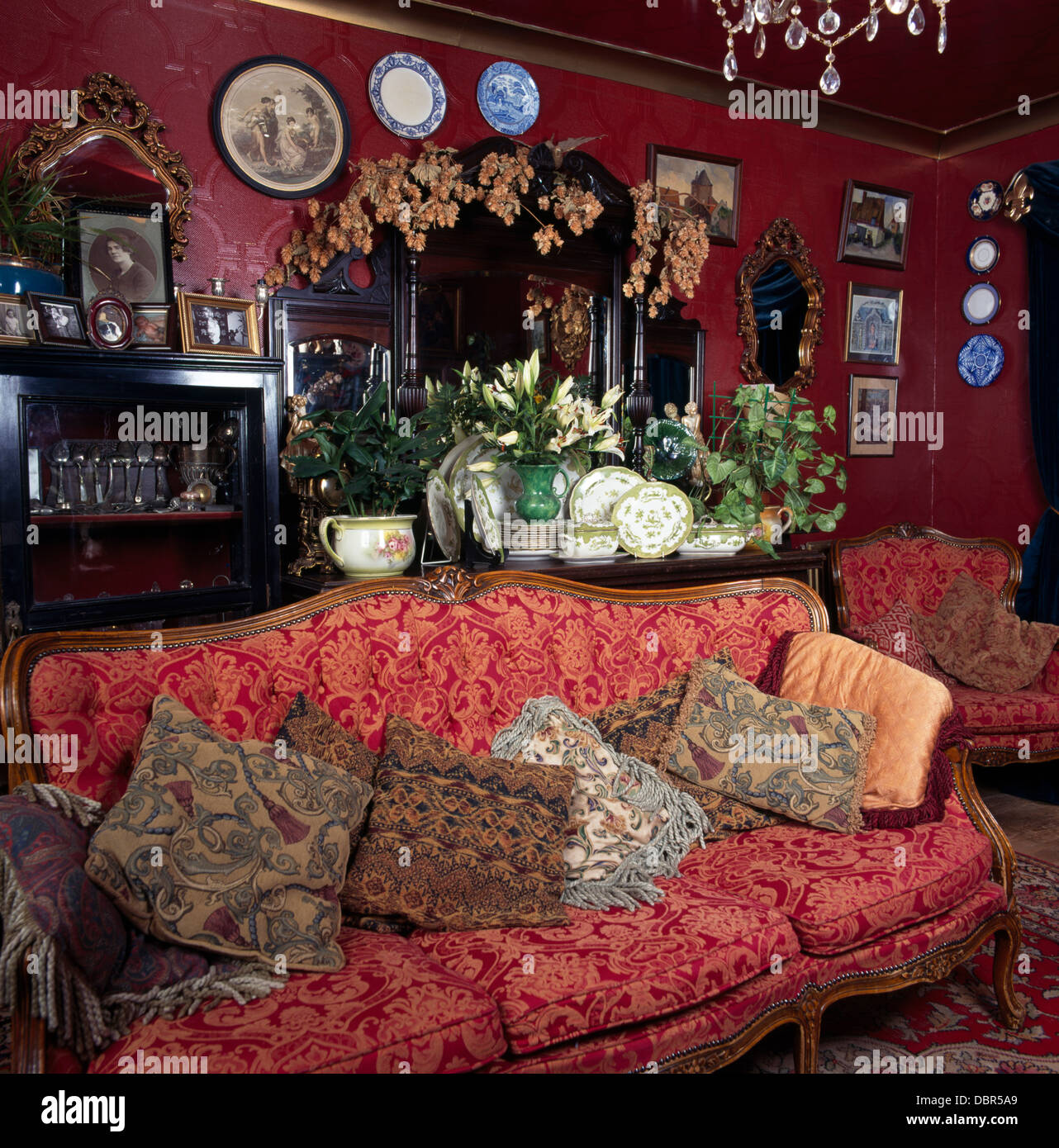 Red patterned French-style sofa piled with cushions in dark red ...