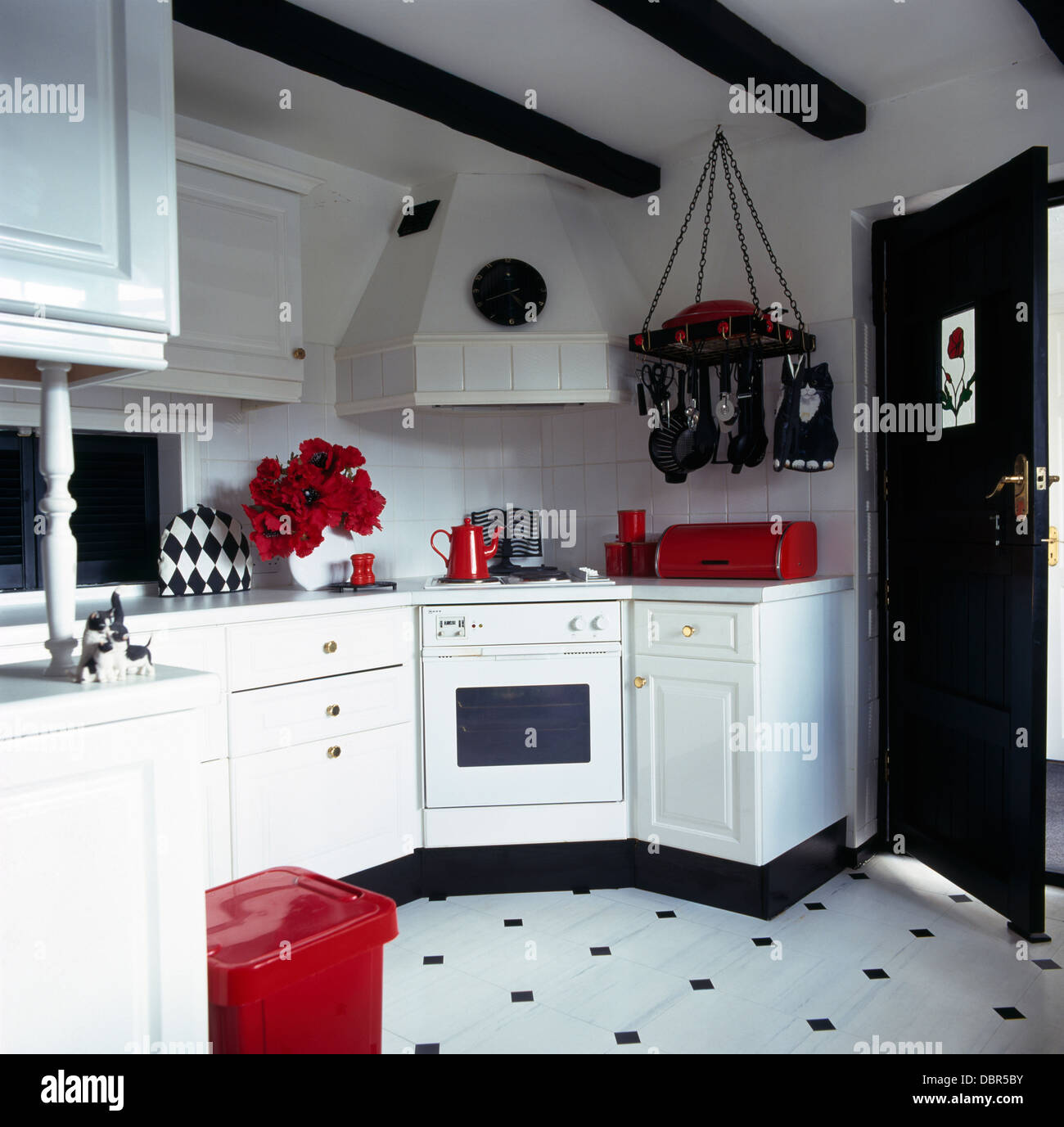 Red accessories in black and white kitchen with black+white vinyl flooring  and metal storage rack