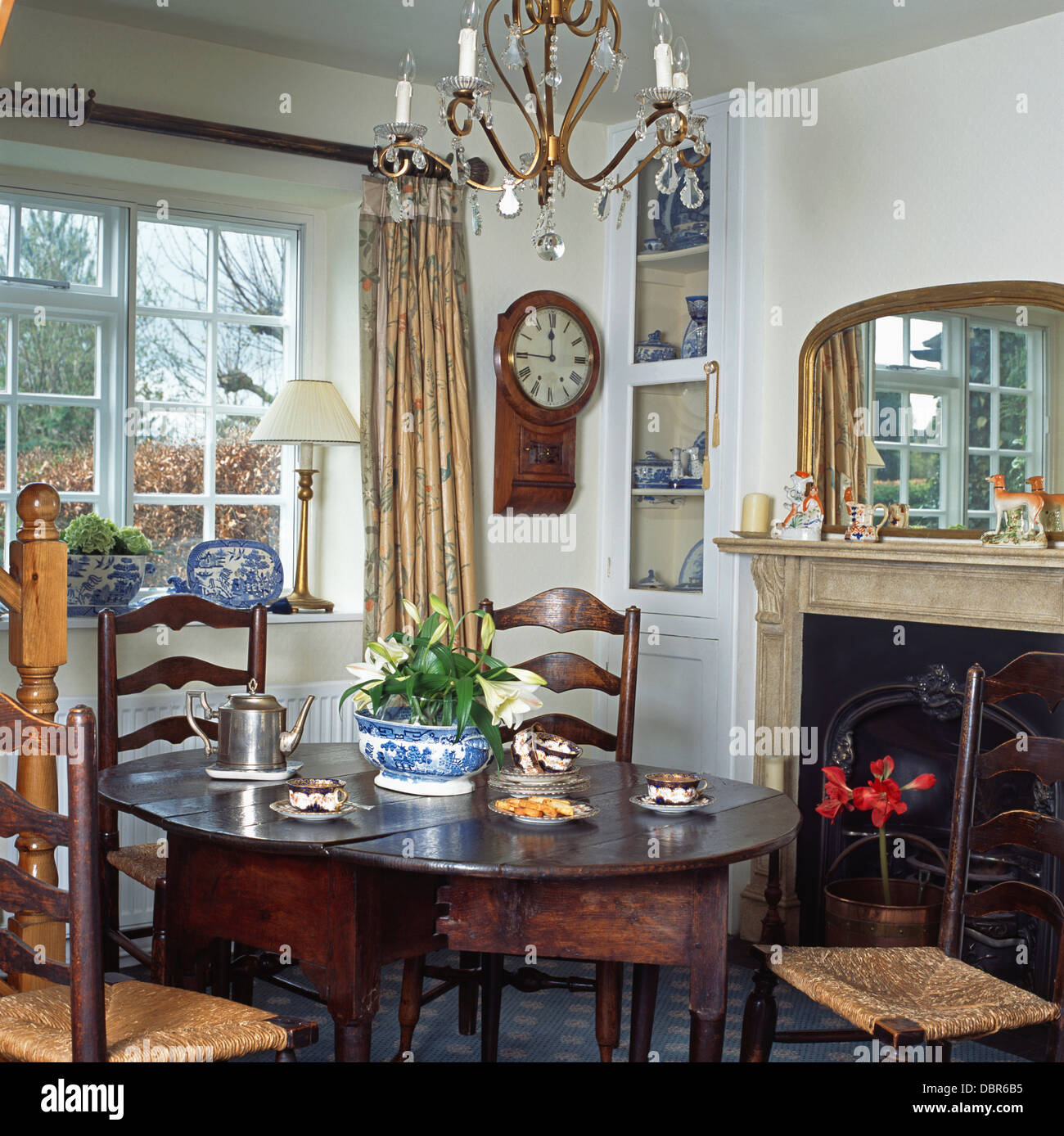 Rush-seated ladder back chairs and antique oak table in front of fireplace  in cottage dining room with wall clock beside window - Rush-seated Ladder Back Chairs And Antique Oak Table In Front Of