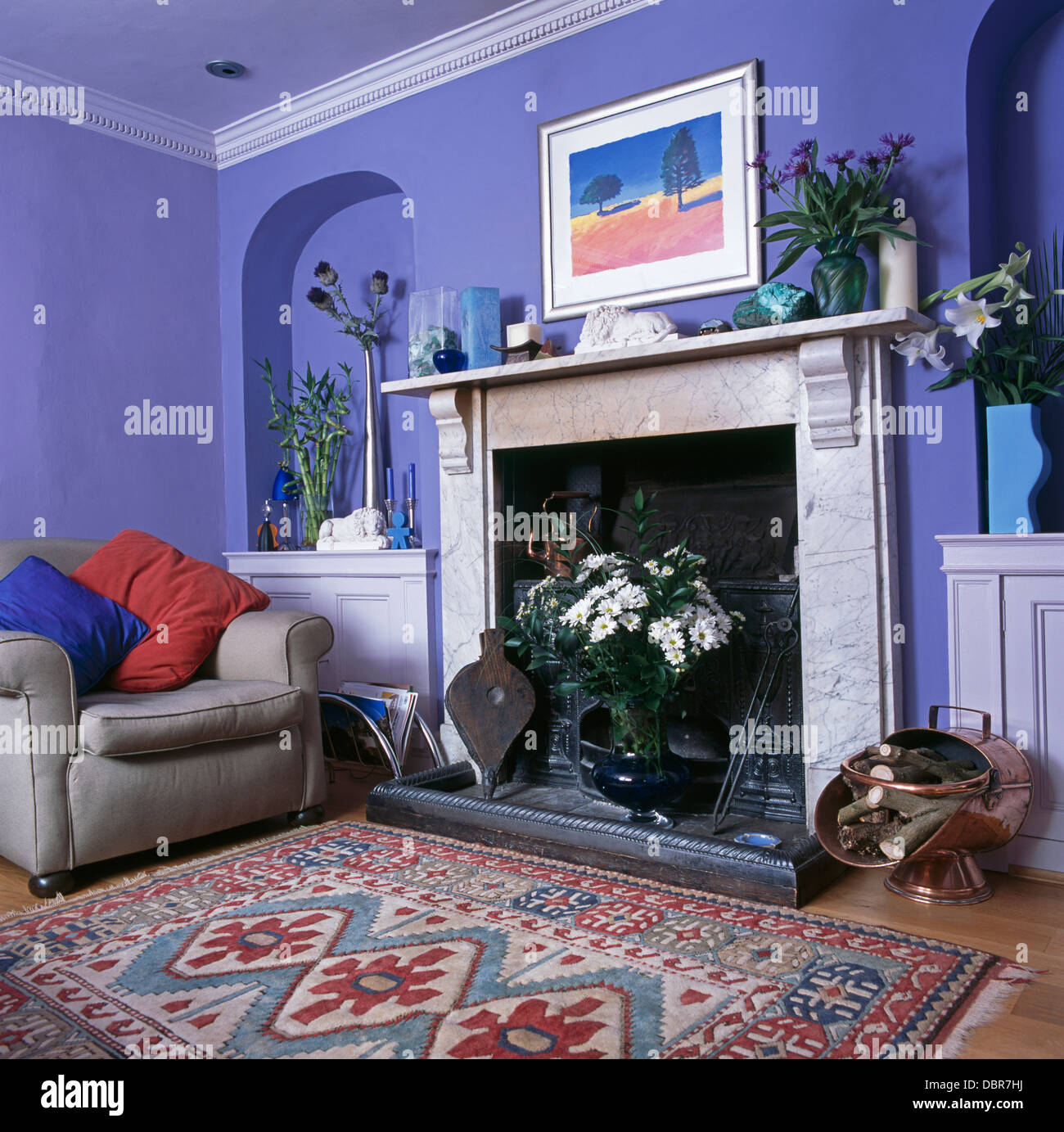 patterned rug in front of marble fireplace in blue living room