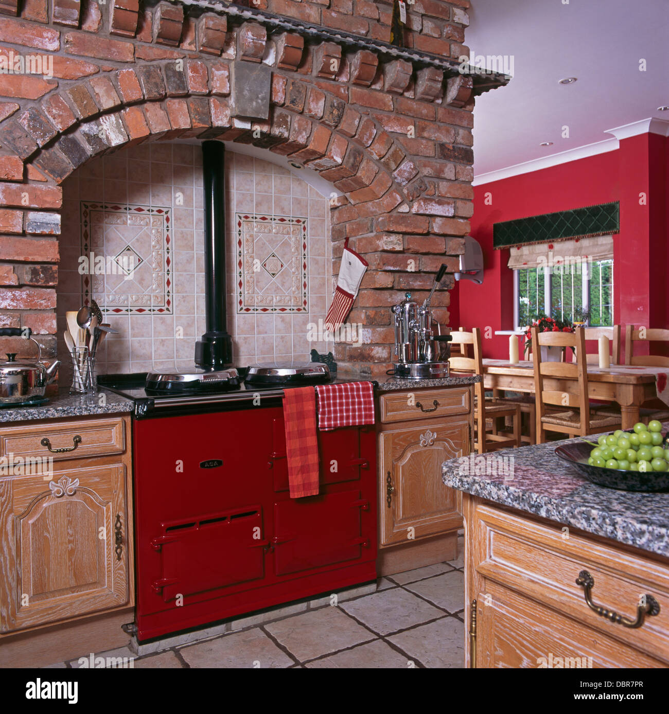 Exposed Brick Wall And Ceramic Wall Tiles Above Red Aga Oven In Large Red Country Kitchen
