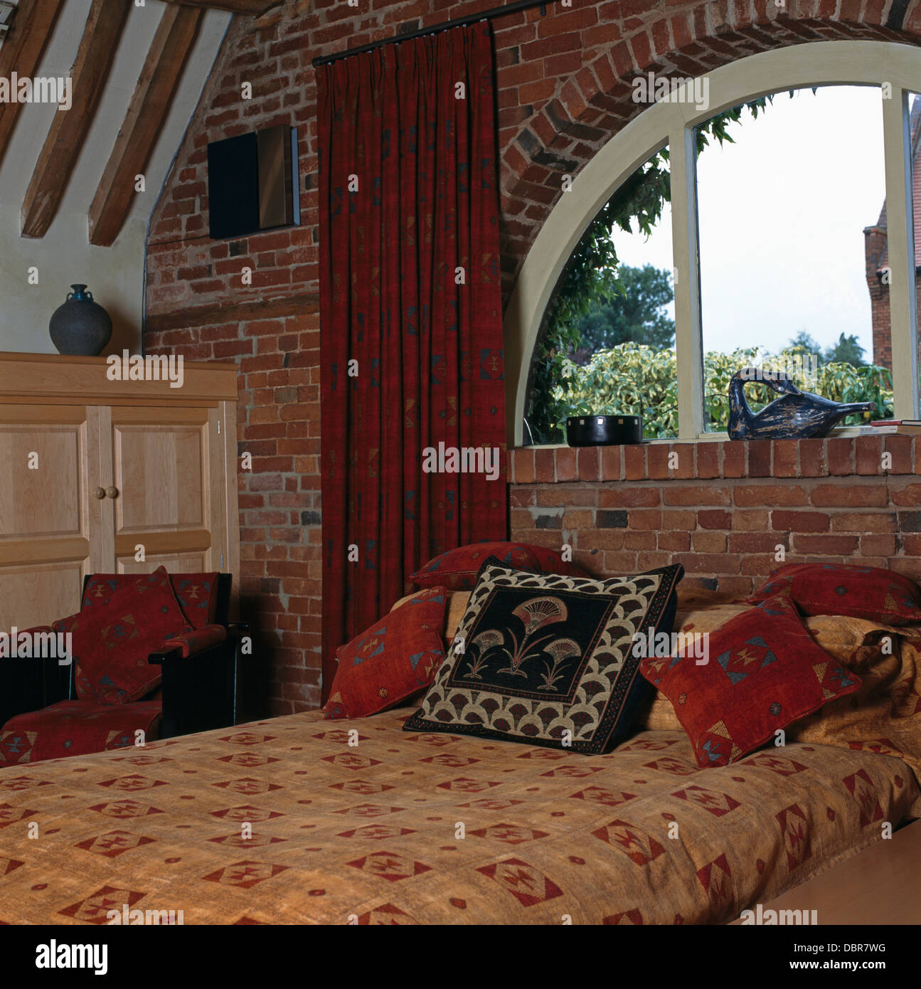 Curtains for half moon windows - Red Curtain And Halfmoon Window Above Bed With Patterned Cushions And Duvet In Barn