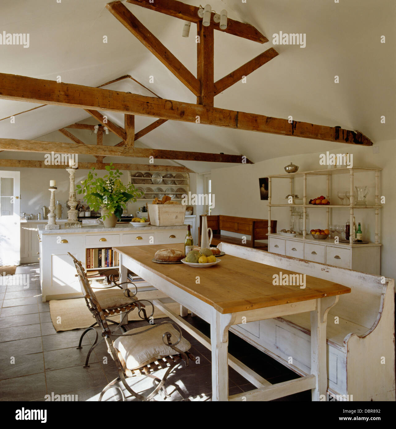 Stock Photo   White Painted Wooden Settle And Metal Chairs At Simple Wood  Table In Barn Conversion Kitchen Dining Room With Stone Floor