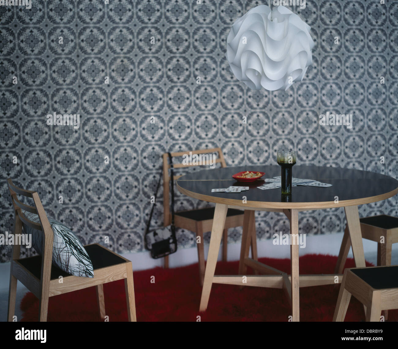 Charmant Folded Plastic Ceiling Light Above Pale Wood Circular Table And Chairs In  Dining Room With Gray Graphic Wallpaper
