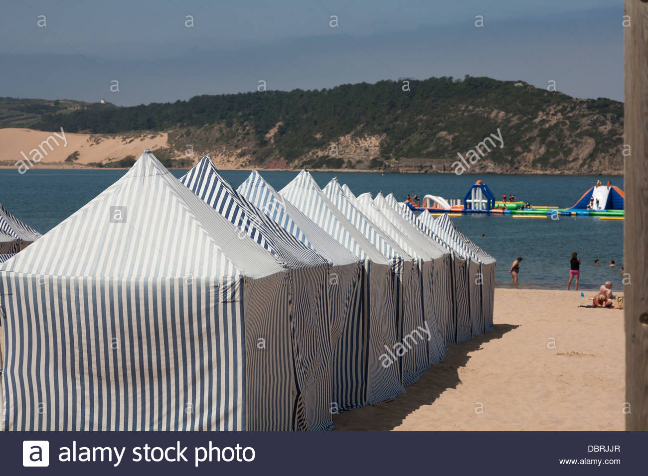a row of blue and white striped beach tents at the coastal resort of Sao Martinho do Porto on the Silver Coast Portugal & a row of blue and white striped beach tents at the coastal resort ...