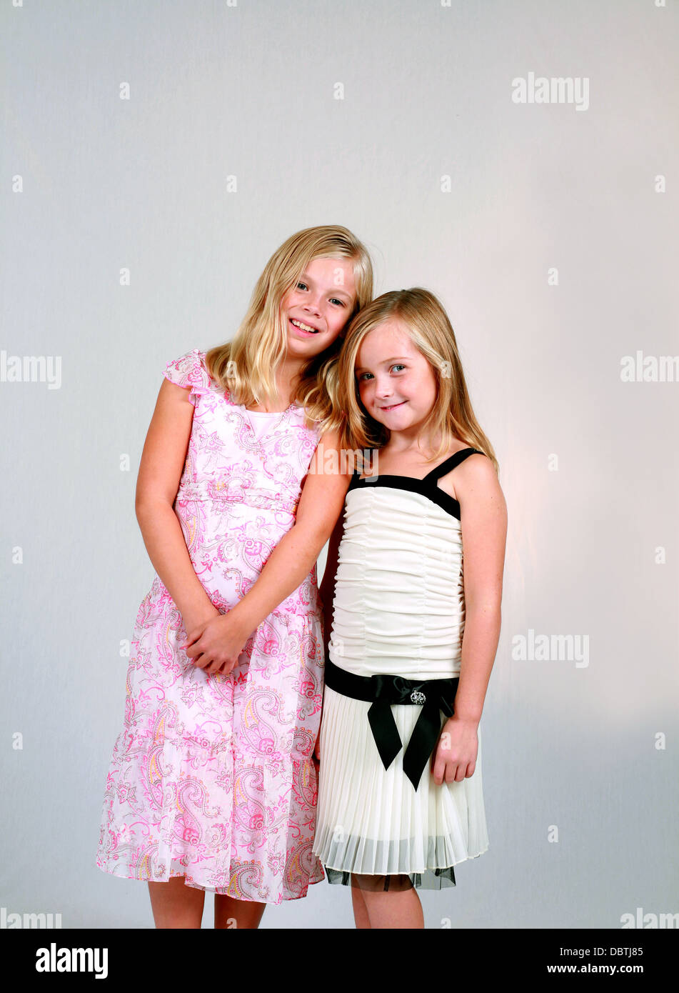 Two Pretty Blonde Preteen Girls In Dresses Smiling Stock