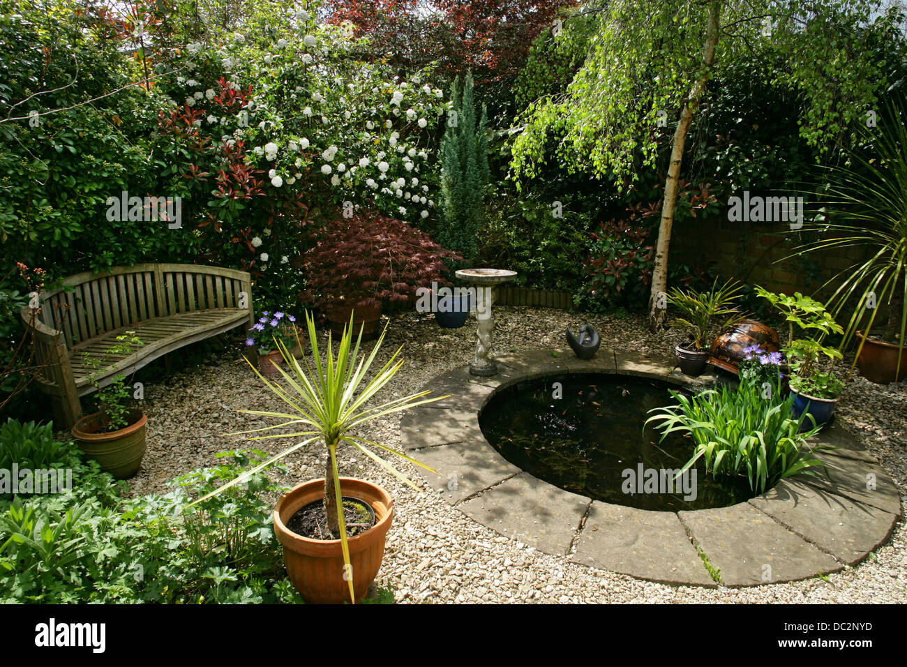 Wooden garden seat and round pond in small english garden for Garden ponds uk