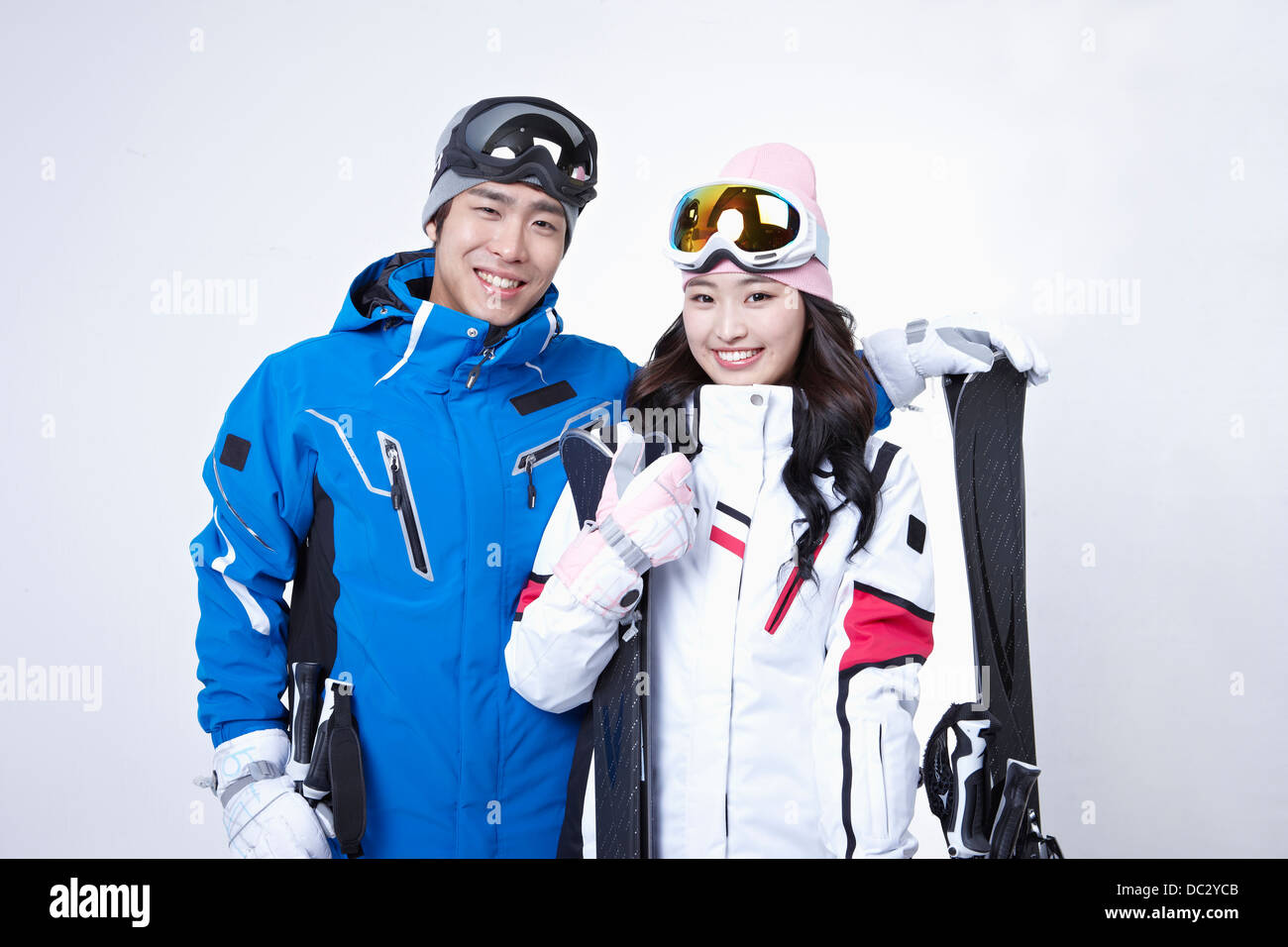 a couple in ski outfit posing in white background