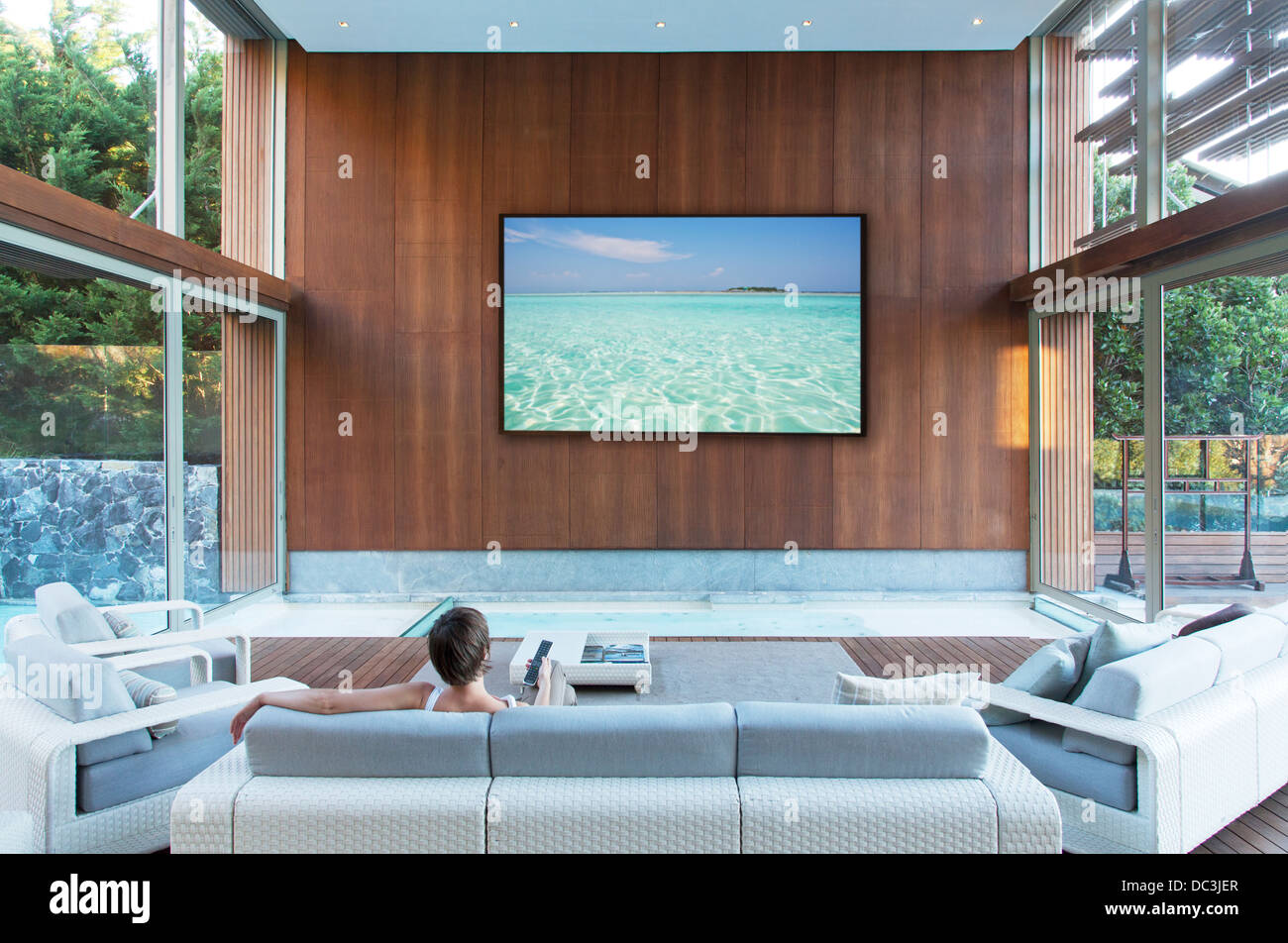 Woman watching large flat screen TV in modern living room Stock ...